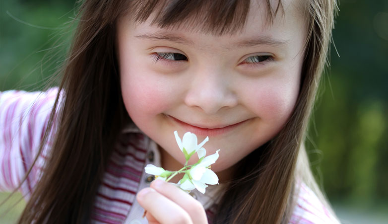 Young Girl holding a flower smiling | Simcoe Community Services