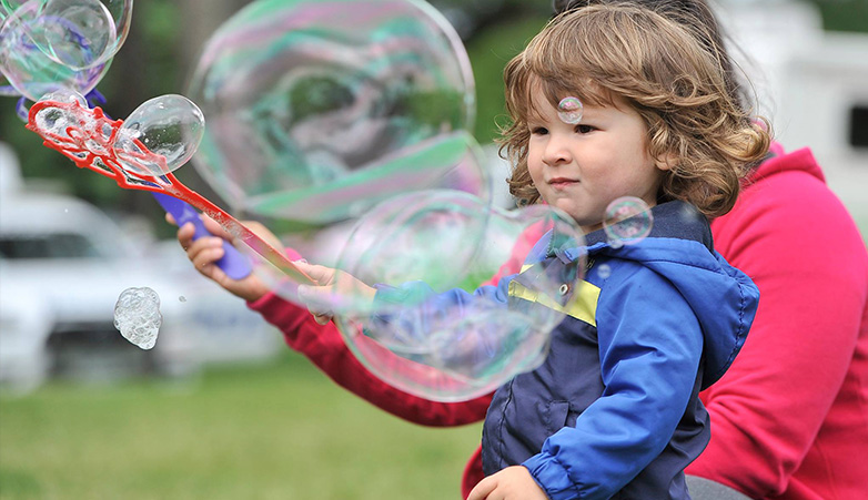 Young child playing with bubbles outside | Simcoe Community Services