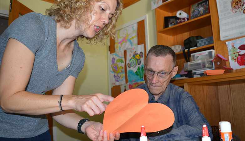 Woman helping an elderly man do arts and crafts | Get Involved | Simcoe Community Services