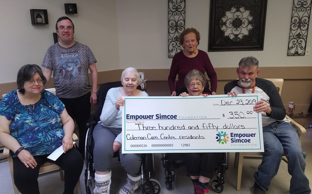 Coleman Residents Council holding up large donation cheque