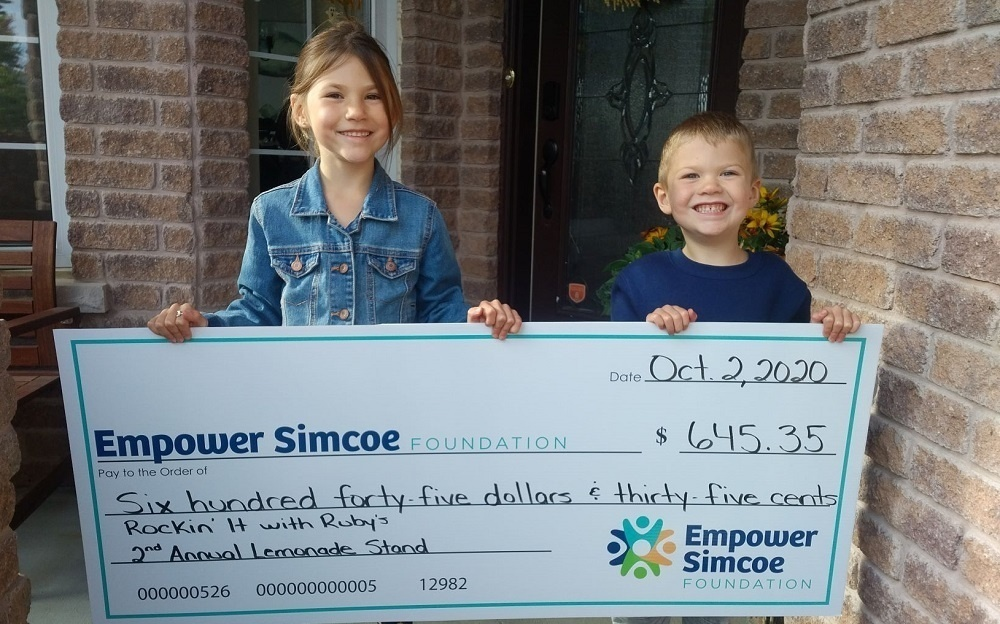 Kids holding up oversized cheque donation